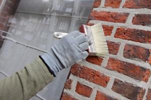Artisan peignant des briques