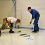 Artisans appliquant peinture epoxy sol.